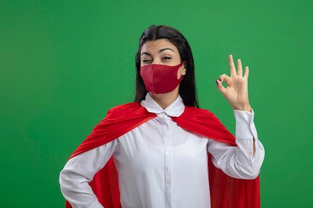Gioiosa oung indoeuropeo supereroe ragazza che indossa la maschera che tiene una mano sul fianco e mostrando il suo segno ok dall'altro lato e ammiccante isolato sul muro verde con spazio di copia