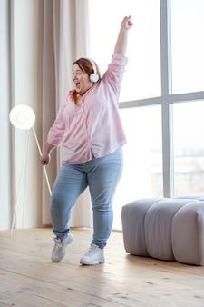 Радостная женщина с избыточным весом танцует под музыку, весело проводя время дома