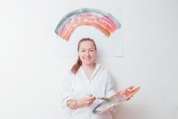 Joyful painter with palette and brush in studio