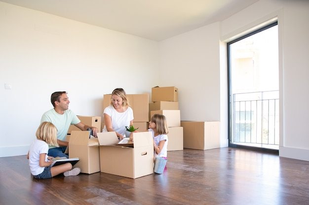 Радостные родители и двое детей распаковывают вещи в новой пустой квартире, сидят на полу и достают предметы из открытых ящиков