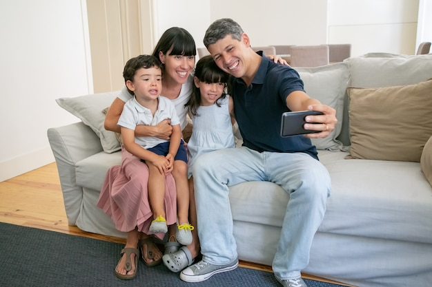 Joyful parents couple and two children sitting on couch at home together, taking selfie