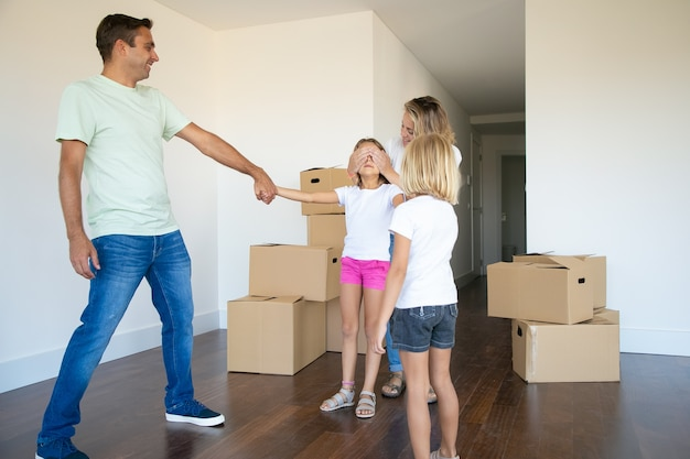 Joyful parents and little sister leading girl with closed eyes in new apartment