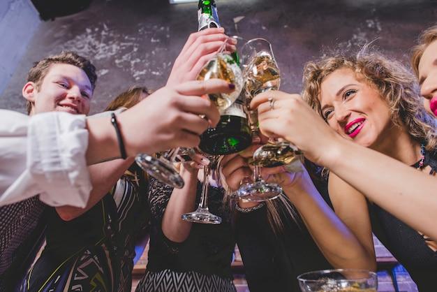 Joyful people clinking glasses