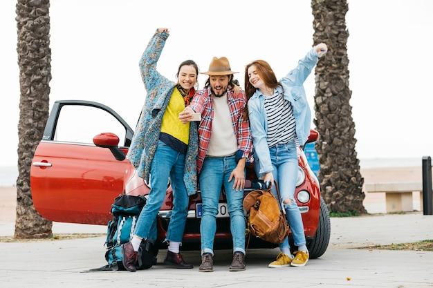 Joyful people taking selfie near red car