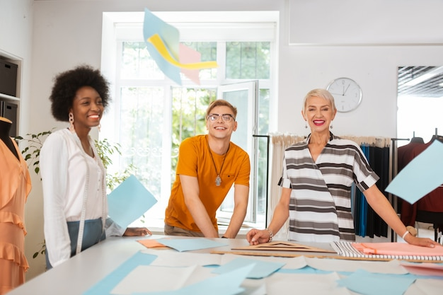 즐거운 사람들. 작업장에 서 있는 행복한 재단사 팀은 앞에서 보면서 웃고 있습니다.
