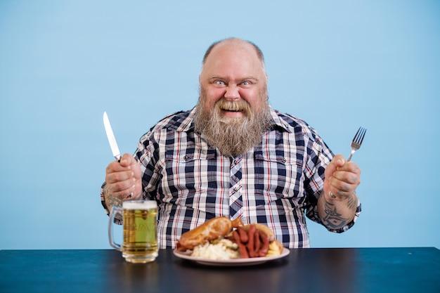 太りすぎのうれしそうな人は青い背景の上の豊富な食品とビールとテーブルに座っています