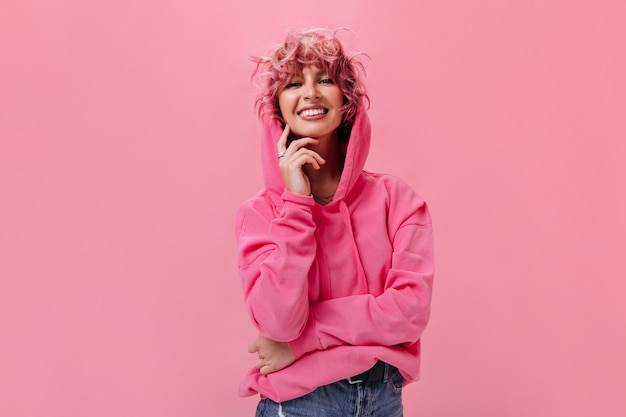 큰 후드티와 청바지를 입은 즐거운 분홍색 머리 곱슬머리 여성은 진심으로 웃고 고립된 분홍색 벽에 얼굴을 만진다