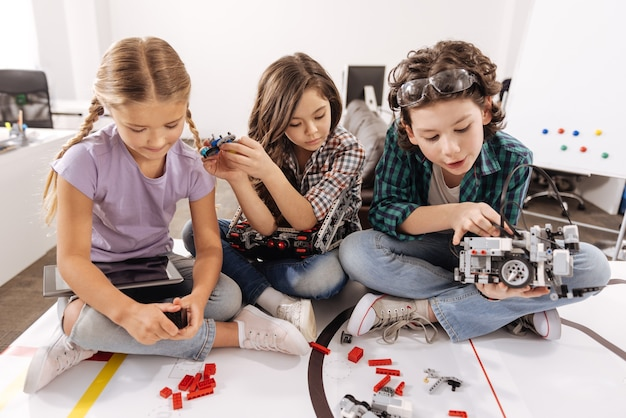 Joyful playful gifted children sitting in the classroom and playing with gadgets and devices while expressing interest