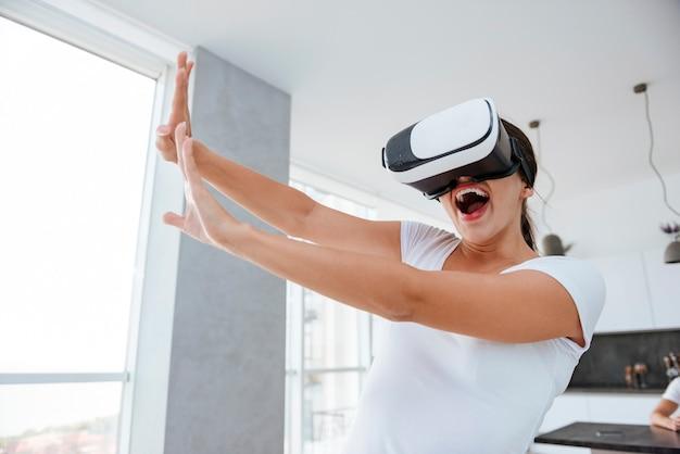 집에서 가상 현실 구글로 컴퓨터 게임을 하는 유쾌하고 쾌활한 젊은 여성