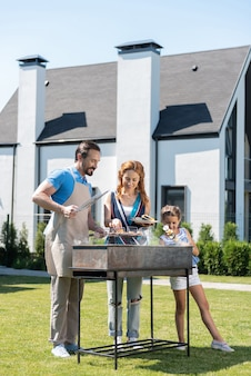 Joyful pleasant family standing together near the grill while enjoying their weekend