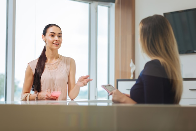 Joyful pleasant woman talking to the administrator while making an appointment