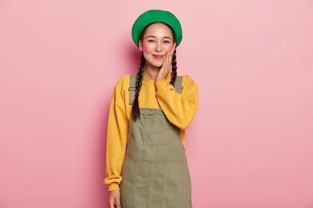 즐거운 만족 갈색 머리 중국 여자는 재미있는 대화를 가지고, 부드럽게 뺨을 만집니다.