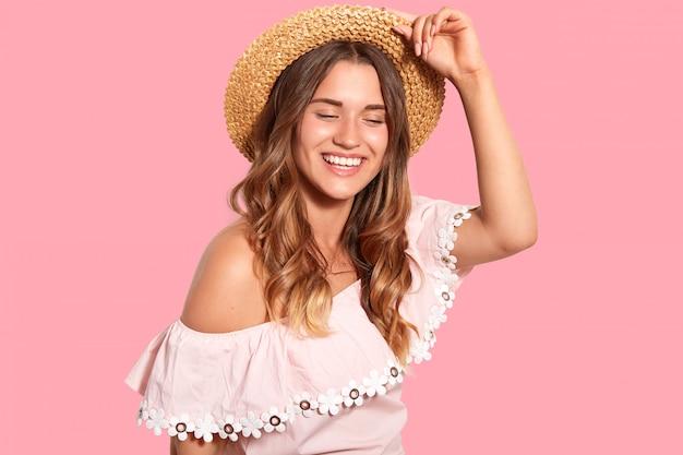 Радостная довольная женщина с зубастой улыбкой, носит головные уборы, модная блузка, хихикает позитивно, наслаждается приятными моментами в жизни, изолированными на розовом. люди, счастье, настроение, концепция