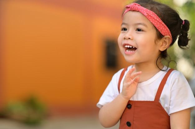 Радостный портрет счастливой маленькой азиатской улыбающейся детской девочки с большой улыбкой и смехом. положительный смех лицо. здоровые счастливые смешные улыбающееся лицо молодой очаровательны прекрасный женский малыш.