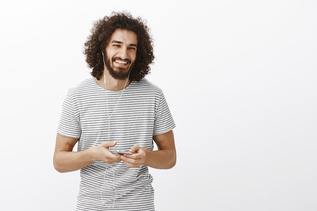 Joyful positive attractive male model in striped t-shirt, laughing happily while holding smartphone and listening music via earphones,