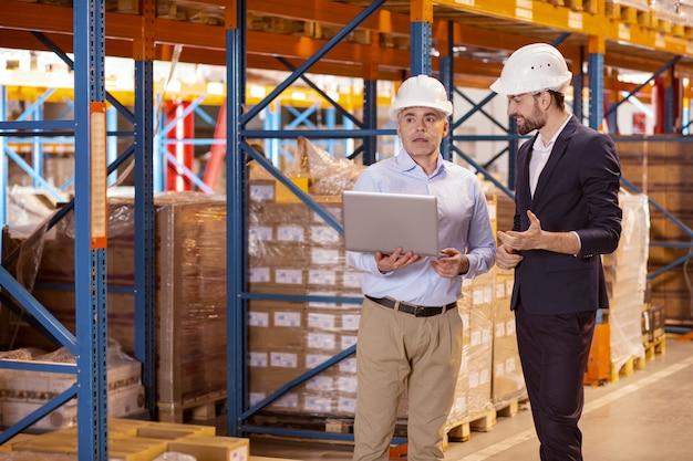 Радостный позитивный бизнесмен разговаривает с менеджером склада, объясняя свои идеи