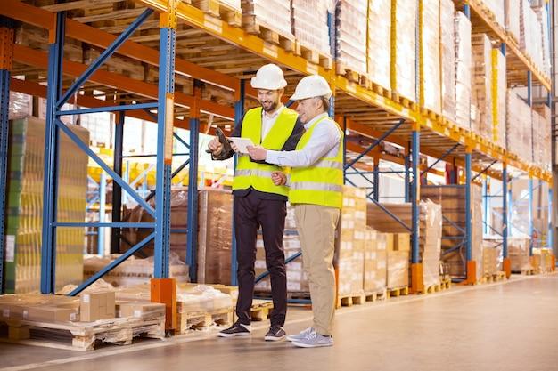 倉庫で働きながら一緒に立っているうれしそうな前向きな同僚