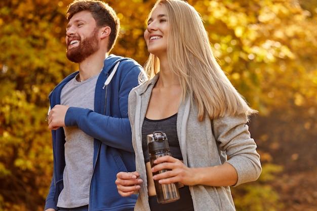 숲이 우거진 숲 지역, 가을 자연에서 실행하는 즐거운 긍정적 인 커플. 남자와 여자 훈련, 운동. 피트니스 건강한 라이프 스타일 컨셉