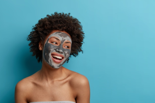 Joyful positive dark skinned curly woman stands naked indoor, applies beauty mud mask for perfect soft facial skin, cares about complexion, looks gladfully away, isolated on blue wall.