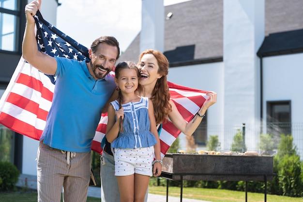 Радостная позитивная семья улыбается вам во время совместного празднования дня независимости