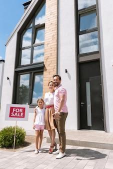 그것을 사는 동안 집 근처에 서있는 즐거운 긍정적 인 가족