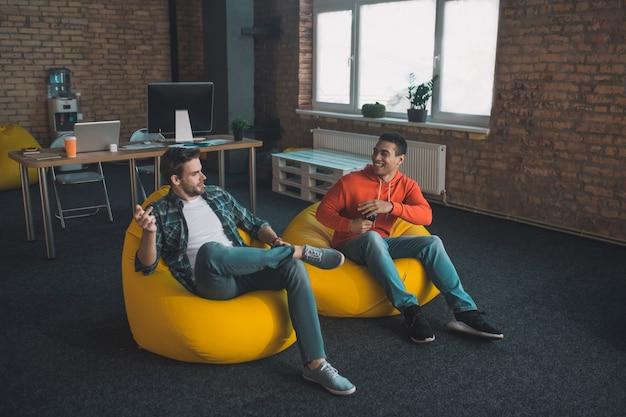 Радостные и позитивные друзья разговаривают друг с другом, сидя в креслах-мешках у себя дома