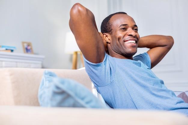 Радостный позитивный красивый мужчина улыбается и наслаждается отдыхом, находясь дома