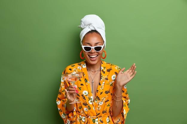 Gioiosa casalinga positiva indossa un asciugamano avvolto sulla testa e un vestito giallo con stampa floreale, beve cocktail, ha un corpo ben curato, isolato sulla parete verde. persone, tempo libero, concetto di bere