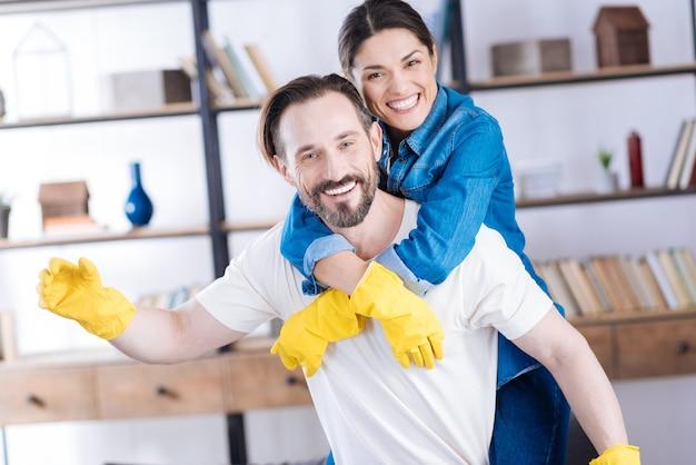 手袋をはめて、夫を抱きしめる妻とうれしそうなポジティブな陽気なカップル