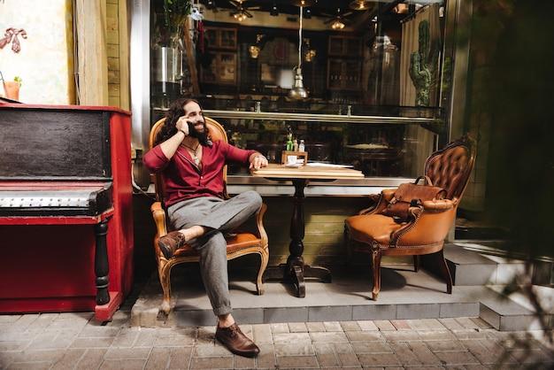 Радостный позитивный человек разговаривает по телефону, сидя за столом
