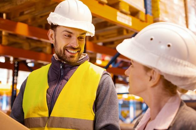 Радостный позитивный мужчина улыбается, глядя на своего коллегу-женщину