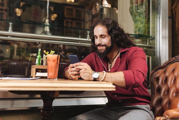 Радостный позитивный мужчина с помощью своего смартфона набирает сообщение