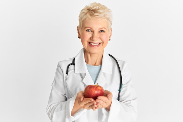 Joyful positive mature female practitioner holding sweet crunchy fruit rich in fiber, phytonutrients and antioxidants, recommending to eat healthy organic food. apple a day keeps doctor away