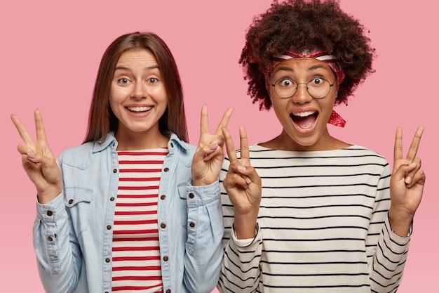 Gioiosa razza mista positiva due giovani donne mostrano il segno di pace con entrambe le mani, sorridono felicemente