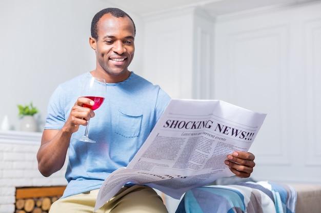 신문에서 충격적인 뉴스를 읽는 동안 웃고 와인을 마시는 즐거운 긍정적 인 좋은 사람