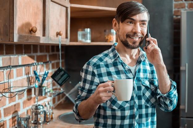 전화로 그의 친구와 이야기하는 동안 웃고 차를 마시고 즐거운 긍정적 인 좋은 사람