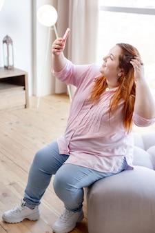 セルフィーを撮りながら髪を整えるうれしそうなポジティブな女性
