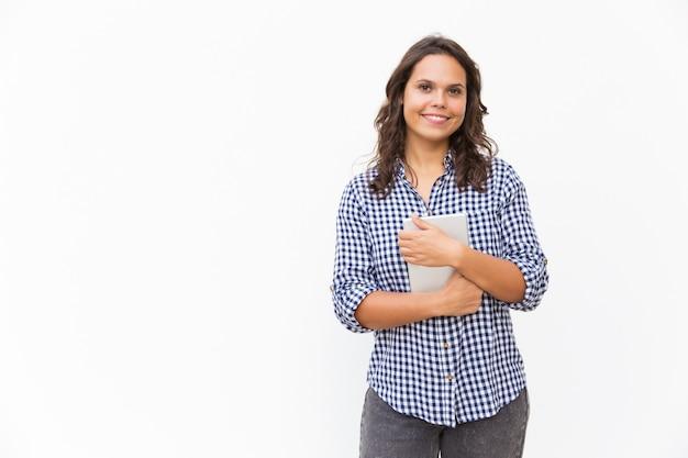 Joyful positive woman holding tablet