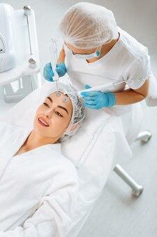 Радостная позитивная женщина улыбается, наслаждаясь процедурой mct