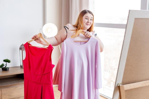 2つの異なるドレスを比較しながら鏡の前に立っているうれしそうなポジティブな女性