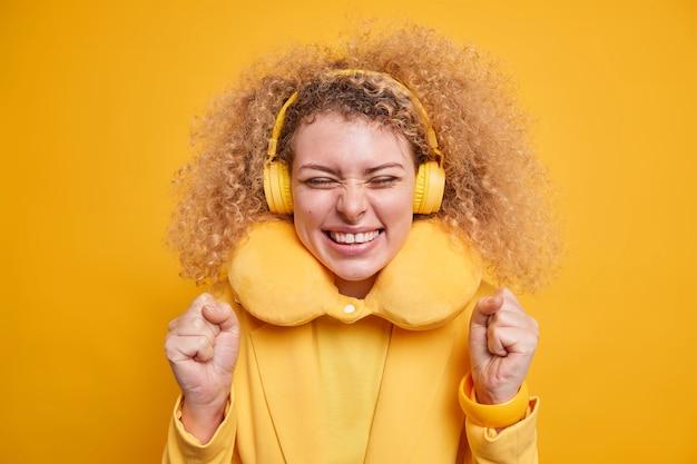 巻き毛のうれしそうなポジティブな女性が首に快適な枕をつけて痛みを和らげるお気に入りの音楽を楽しむワイヤレスヘッドホンを使用して黄色い壁に隔離された幸せを表現する
