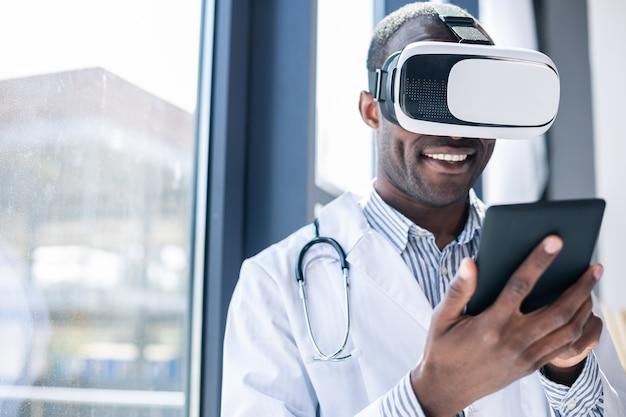 窓の近くに立って、喜んでタブレットをテストするうれしそうな開業医