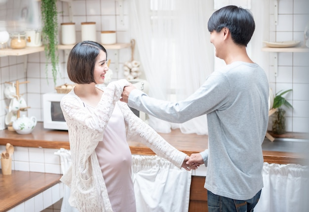 Joyful pregnant asian couple have fun, dancing next to window in kitchen at home, with copy space.health care and love of pregnancy mother's day concept.