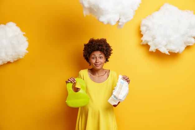 Joyful pregnant woman has afro hair, holds diaper and rubber bib for baby, dressed in casual dress, prepares for child birth, buys all necessary things for newborn, isolated on yellow .