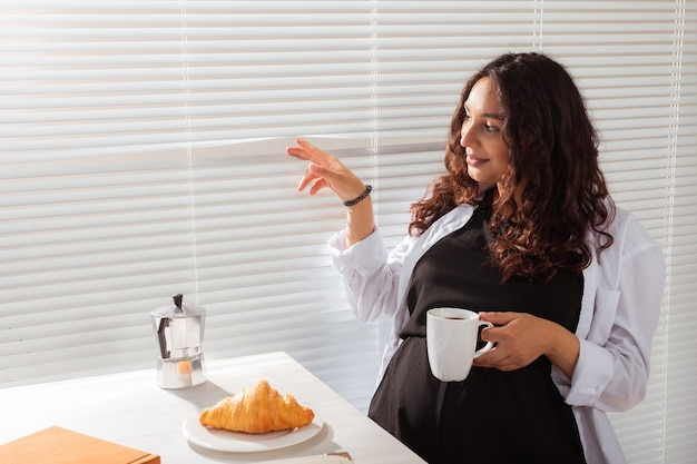 うれしそうな妊娠中の若い美しい女性は、コーヒーとクロワッサンで朝の朝食中にブラインドをのぞきます。おはようのコンセプトと赤ちゃんとの出会いを待っています。コピースペース