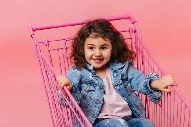 Joyful preteen girl sitting in shopping cart. studio shot of adorable child in denim jacket.