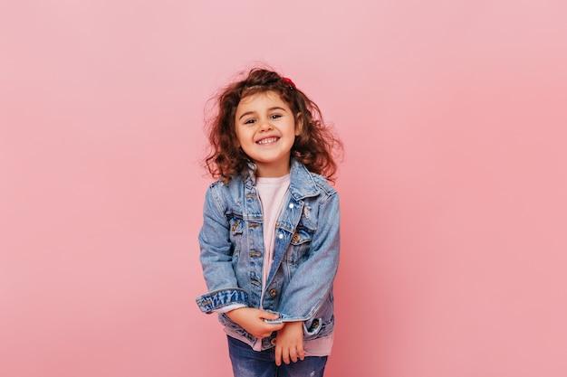 カメラで笑っている巻き毛のうれしそうなプレティーンの子供。ピンクの背景に分離されたのんきな少女のスタジオショット。