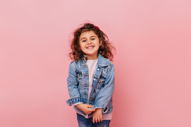 Joyful preteen kid with curly hair laughing at camera. studio shot of carefree little girl isolated on pink background.