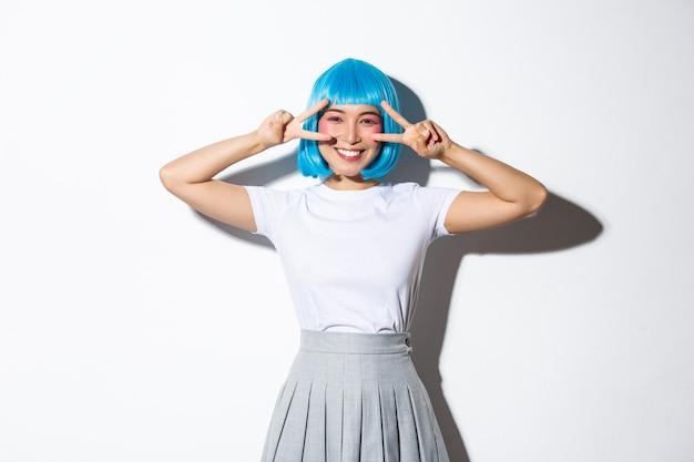 青いパーティーのかつらでうれしそうなかわいいアジアの女性、イベントを祝って、平和のジェスチャーを示し、幸せに笑って、立っています。