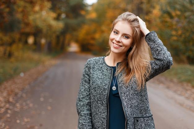 トレンディな灰色のコートを持つうれしそうなかなり美しい若い女性
